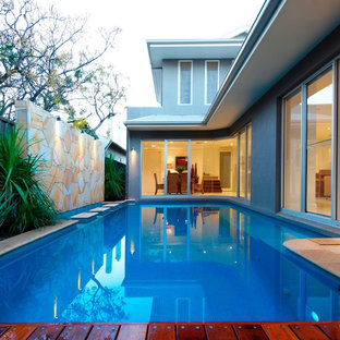 This is an example of a contemporary backyard rectangular lap pool in Adelaide with natural stone pavers.