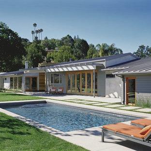 Foto de piscina actual, rectangular, en patio trasero, con adoquines de hormigón