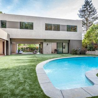 Diseño de piscina con fuente actual, grande, tipo riñón, en patio lateral, con adoquines de hormigón