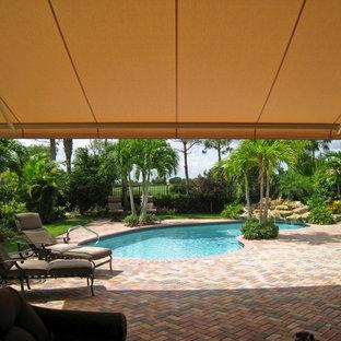 Ejemplo de piscina con fuente alargada, tropical, de tamaño medio, tipo riñón, en patio trasero, con adoquines de ladrillo