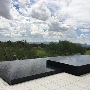 Imagen de piscina con fuente infinita, contemporánea, grande, a medida, en patio trasero, con suelo de baldosas