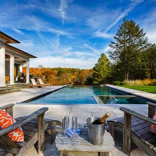 Foto de piscinas y jacuzzis infinitos, tradicionales, grandes, rectangulares, en patio trasero, con losas de hormigón