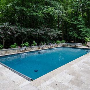 Modelo de piscina con fuente alargada, de estilo americano, grande, rectangular, en patio trasero, con adoquines de piedra natural