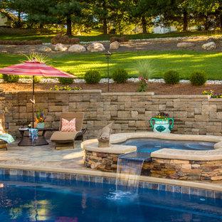 Réalisation d'une grand piscine naturelle et arrière tradition sur mesure avec un bain bouillonnant et des pavés en pierre naturelle.