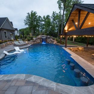 Cette photo montre une très grand piscine naturelle et arrière exotique sur mesure avec un aménagement paysager autour d'une piscine et des pavés en brique.