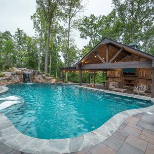 Modelo de piscina natural, exótica, extra grande, a medida, en patio trasero, con adoquines de ladrillo