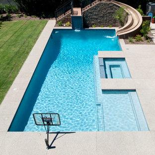 Ejemplo de piscina con tobogán actual, de tamaño medio, rectangular, en patio trasero, con adoquines de hormigón