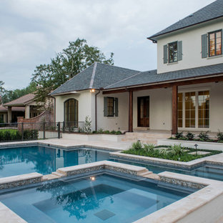 This is an example of an expansive country backyard rectangular pool in New Orleans with a hot tub and tile.