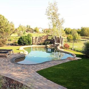 Foto de piscina alargada, contemporánea, grande, a medida, en patio trasero, con adoquines de ladrillo