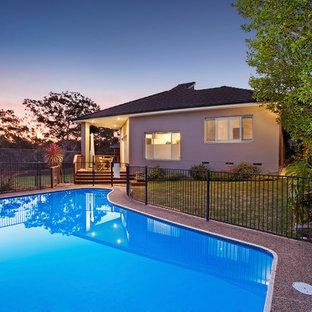 Imagen de piscina alargada, tradicional renovada, de tamaño medio, en forma de L, en patio trasero, con granito descompuesto