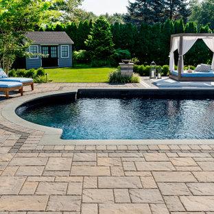 Diseño de piscina tradicional, en patio trasero, con adoquines de hormigón