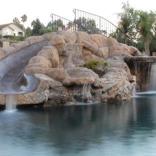 Diseño de piscina con tobogán tradicional, grande, a medida, en patio trasero, con suelo de hormigón estampado