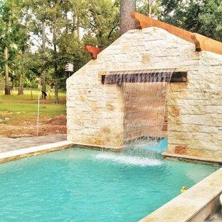 Esempio di una piscina rustica rettangolare di medie dimensioni e dietro casa con fontane e pavimentazioni in pietra naturale