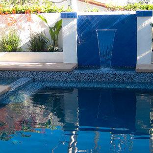 """Esempio di una piscina fuori terra classica a """"L"""" di medie dimensioni e dietro casa con fontane e lastre di cemento"""