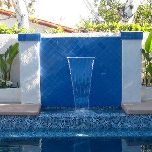 """Idee per una piscina fuori terra tradizionale a """"L"""" di medie dimensioni e dietro casa con fontane e lastre di cemento"""