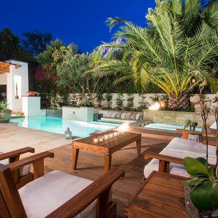 Modelo de piscina actual, pequeña, rectangular, en patio trasero, con losas de hormigón
