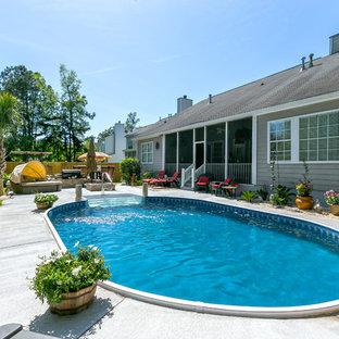 Foto de piscina costera, en patio trasero, con losas de hormigón