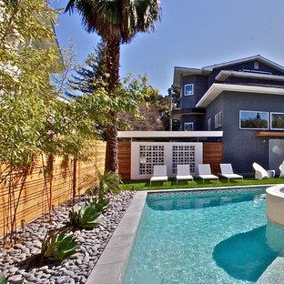 Imagen de piscinas y jacuzzis alargados, retro, de tamaño medio, en forma de L, en patio trasero, con adoquines de piedra natural