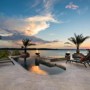 Свежая идея для дизайна: бассейн-инфинити произвольной формы на заднем дворе в морском стиле с джакузи и покрытием из каменной брусчатки - отличное фото интерьера