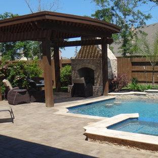 Foto de piscina con fuente alargada, clásica, grande, a medida, en patio trasero, con adoquines de ladrillo