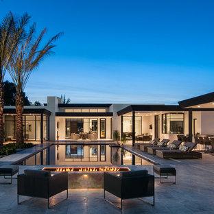 Foto de piscinas y jacuzzis infinitos, contemporáneos, rectangulares, en patio trasero, con suelo de baldosas