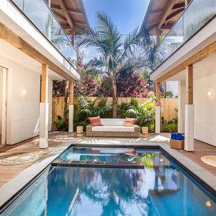 Esempio di una piscina monocorsia tropicale rettangolare in cortile con una vasca idromassaggio e pedane