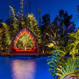 サンディエゴの巨大なオーダーメイドトロピカルスタイルのおしゃれなプール (天然石敷き) の写真