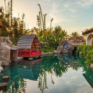Foto di un'ampia piscina naturale tropicale personalizzata dietro casa con un acquascivolo e pavimentazioni in pietra naturale