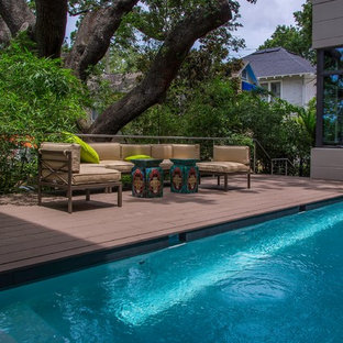 Design ideas for a small modern side yard rectangular pool in Tampa with decking.