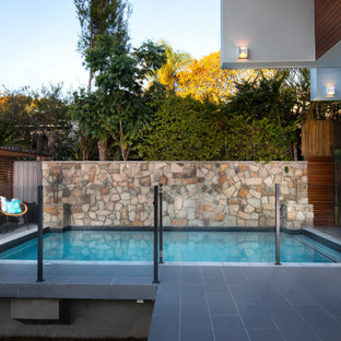 Mid-sized contemporary backyard rectangular pool in Brisbane with tile.