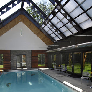 Large contemporary indoor rectangular pool in New York with a pool house and concrete slab.