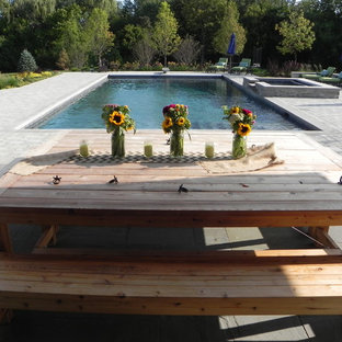 This is an example of a country backyard l-shaped pool in Chicago with a pool house and natural stone pavers.