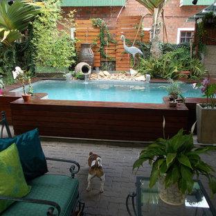 Ejemplo de piscina con fuente elevada, exótica, de tamaño medio, rectangular, en patio, con entablado