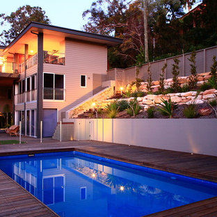 This is an example of a large tropical side yard rectangular pool in Sydney with decking.