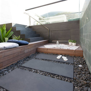 Inspiration for a mid-sized modern rooftop rectangular infinity pool in Hong Kong with a pool house and natural stone pavers.
