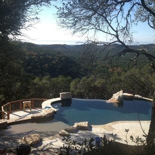 """Ispirazione per una piscina a sfioro infinito minimalista a """"C"""" di medie dimensioni e dietro casa con fontane e pedane"""