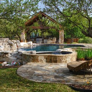Ejemplo de piscinas y jacuzzis naturales, clásicos, de tamaño medio, a medida, en patio trasero, con adoquines de piedra natural