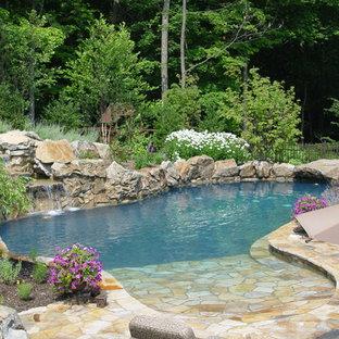 Cette photo montre une grand piscine naturelle et arrière chic sur mesure avec un point d'eau et des pavés en pierre naturelle.