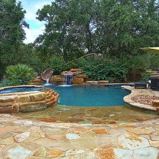 Foto di una piscina naturale costiera personalizzata di medie dimensioni e dietro casa con pavimentazioni in pietra naturale e una vasca idromassaggio