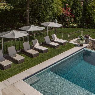 Large minimalist backyard tile and custom-shaped infinity hot tub photo in New York