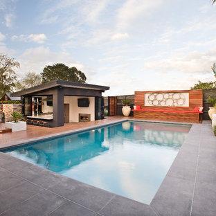 Ispirazione per una grande piscina monocorsia contemporanea rettangolare dietro casa con pavimentazioni in cemento