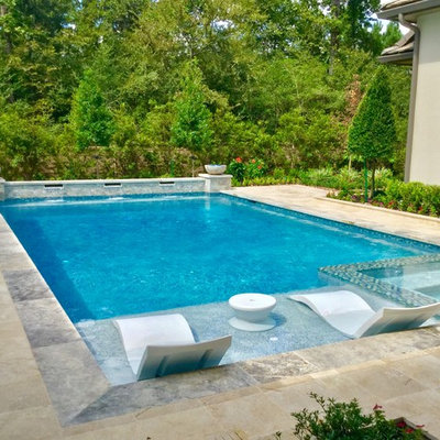 Example of a large transitional backyard stone and rectangular lap pool fountain design in Houston