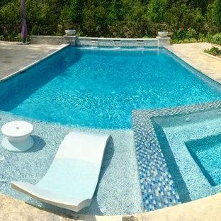 Immagine di una grande piscina monocorsia chic rettangolare dietro casa con fontane e pavimentazioni in pietra naturale