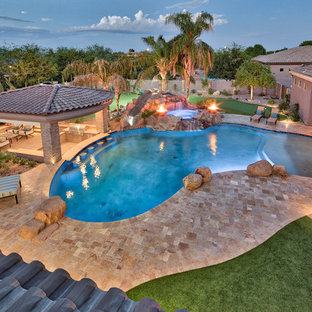 Photo of a large mediterranean backyard natural pool in Phoenix with natural stone pavers.