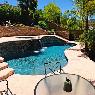 Pool - mid-sized mediterranean backyard stamped concrete and custom-shaped aboveground pool idea in Los Angeles