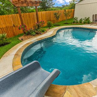 """Esempio di una piscina naturale tropicale a """"C"""" di medie dimensioni e dietro casa con un acquascivolo e lastre di cemento"""