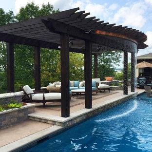 Immagine di una piscina monocorsia chic rettangolare dietro casa con fontane e lastre di cemento