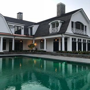 Modelo de piscina infinita, actual, rectangular, en patio trasero, con adoquines de piedra natural