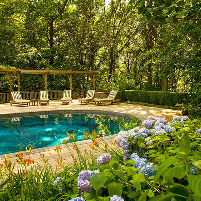Example of a mid-sized classic brick and round pool design in New York