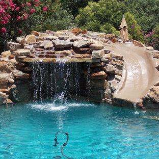 Immagine di una piscina naturale moderna personalizzata di medie dimensioni e dietro casa con pedane e un acquascivolo